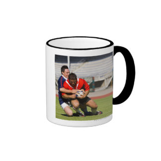 Rugby players fighting for ball mugs