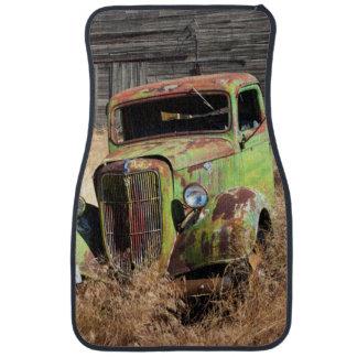 Rusting car in front of abandoned farm car mat
