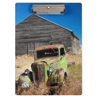 Rusting car in front of abandoned farm clipboard