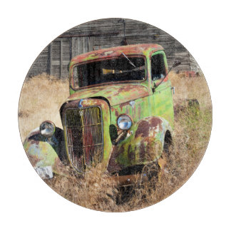 Rusting car in front of abandoned farm cutting board