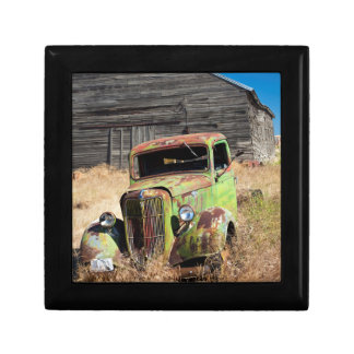Rusting car in front of abandoned farm gift box