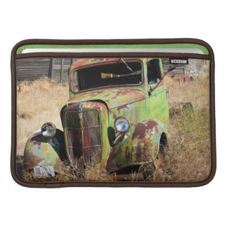 Rusting car in front of abandoned farm MacBook sleeve