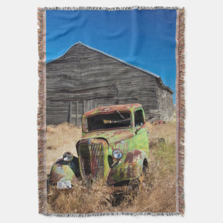 Rusting car in front of abandoned farm throw blanket