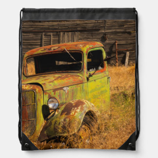 Rusting green truck in front of abandoned farm drawstring bag
