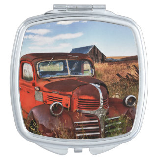 Rusting orange Dodge truck with abandoned farm Travel Mirror