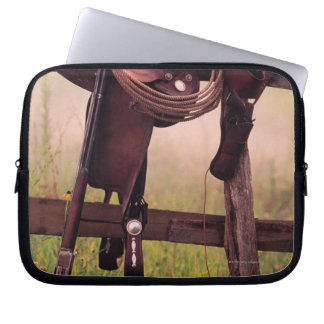 Saddle and lasso on fence computer sleeve