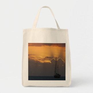 Sailboat at sunset tote canvas bags