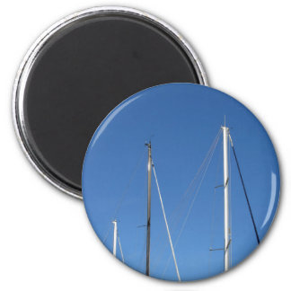 Sailboat masts in the marina against a blue sky 6 cm round magnet
