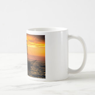 Sailing boat in silhouette at sunset coffee mug