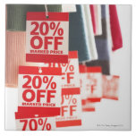 Sale tags attached to hanging clothes, close-up tile