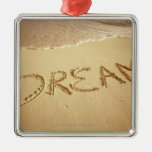 Sand writing 'Dream' with incoming surf at top