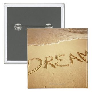 Sand writing 'Dream' with incoming surf at top Button