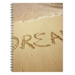Sand writing 'Dream' with incoming surf at top Spiral Notebook