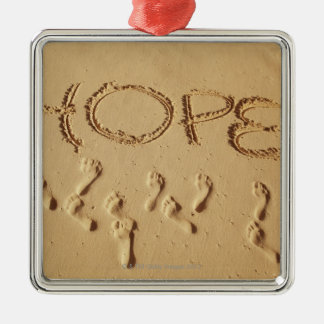 Sand writing ' Hope' on the beach with the Christmas Ornament