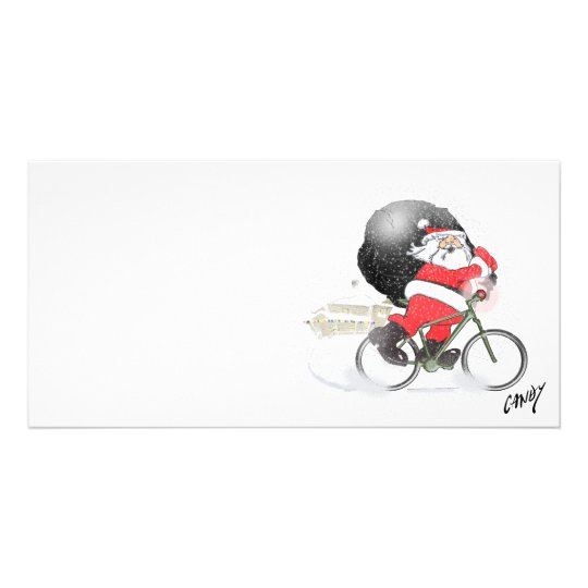 Santa bicycling with his sack in the snow.
