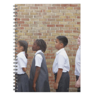 School children lining up in the playground for spiral notebooks