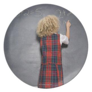 School girl (6-7) writing on blackboard, dinner plate