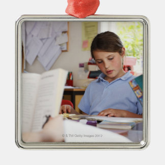 schoolgirl concentrating on reading in class Silver-Colored square decoration
