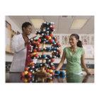 Science teacher and teenage girl looking at postcard