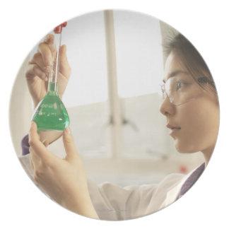 Scientist examining liquid in beaker plate
