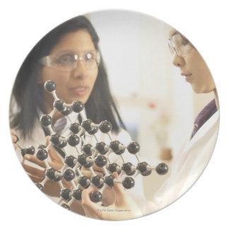 Scientists examining molecular model party plates