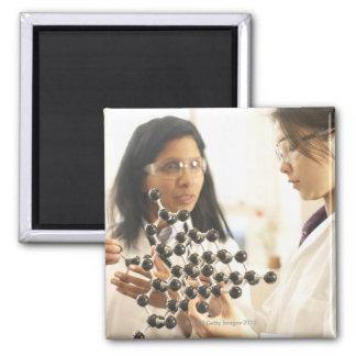 Scientists examining molecular model square magnet