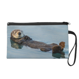 Sea otter floating on back in ocean wristlet clutch