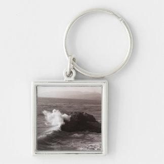 Sea waves crashing against rock key ring