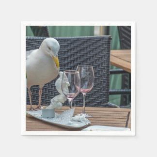 Seagull and empty wine glasses disposable serviettes