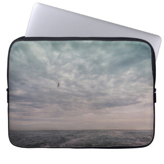Seagull flying under a cloudy sky laptop sleeve