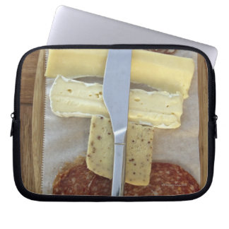 Selection of gourmet cheeses and cut meats laptop sleeve
