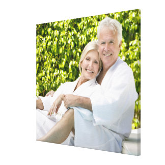 Senior Caucasian couple in robes in spa. Canvas Print