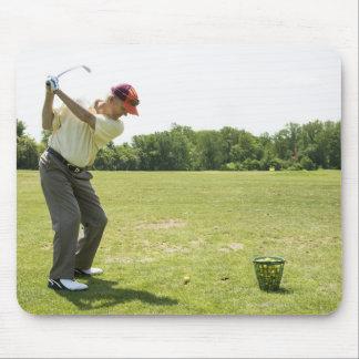 Senior golfer hitting practice balls at a range mouse pad