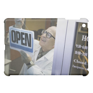 Senior male pharmacist hanging 'Open' sign in Case For The iPad Mini