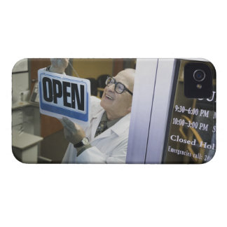 Senior male pharmacist hanging 'Open' sign in iPhone 4 Case