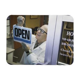 Senior male pharmacist hanging 'Open' sign in Magnet