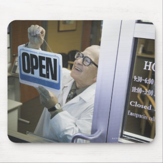 Senior male pharmacist hanging 'Open' sign in Mouse Pad