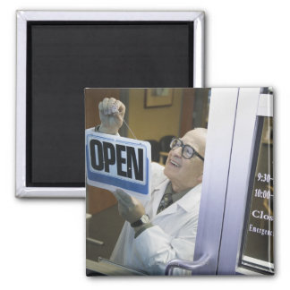 Senior male pharmacist hanging 'Open' sign in Square Magnet