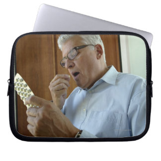 Senior man taking pill laptop sleeve