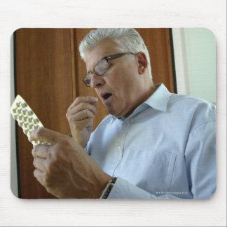 Senior man taking pill mouse pad