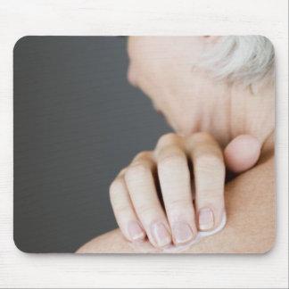 Senior woman applying moisturising cream to her mouse mat