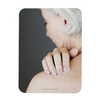 Senior woman applying moisturising cream to her rectangular photo magnet