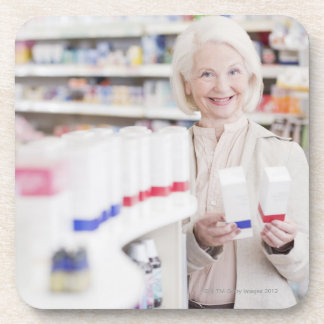 Senior woman comparing packages in drug store coaster