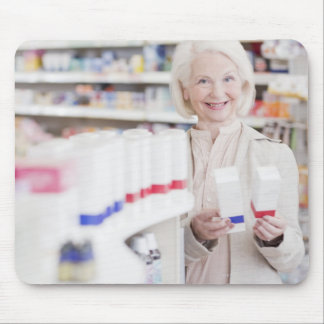 Senior woman comparing packages in drug store mouse pad