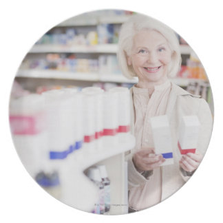 Senior woman comparing packages in drug store plate