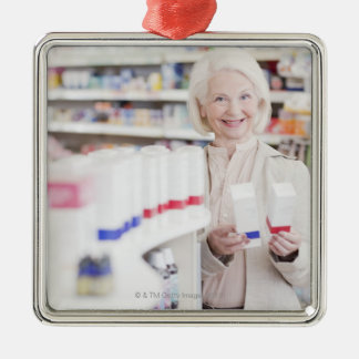 Senior woman comparing packages in drug store Silver-Colored square decoration
