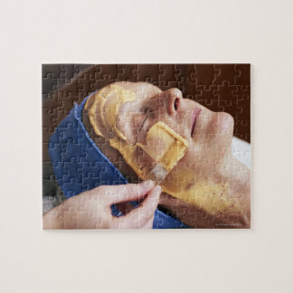 Senior woman having facial cream applied jigsaw puzzle