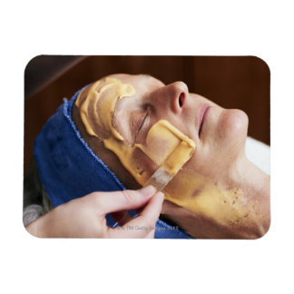 Senior woman having facial cream applied rectangular photo magnet