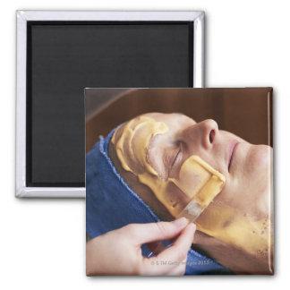 Senior woman having facial cream applied square magnet