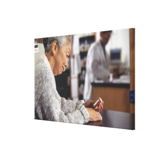 Senior woman in pharmacy reading medicine bottle canvas print